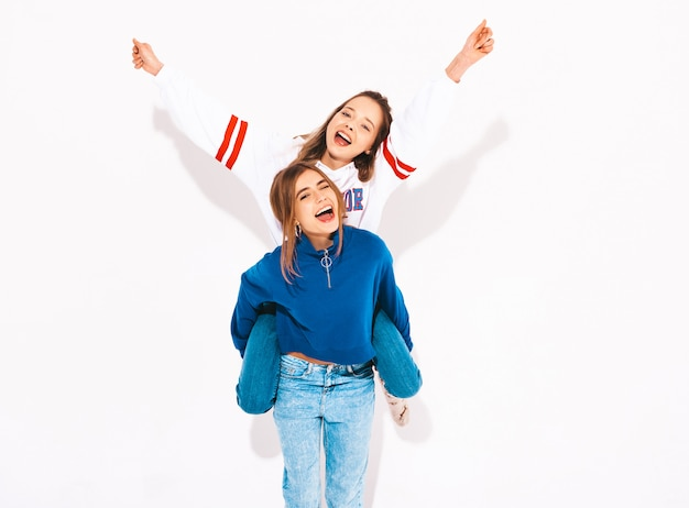 Two young beautiful smiling girls in trendy summer clothes. carefree women. positive model sitting on her friend's back and raising hands Free Photo