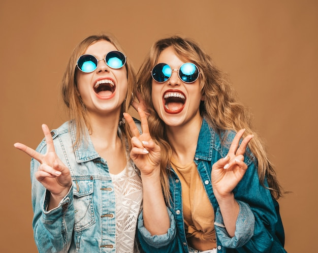 Two young beautiful smiling girls in trendy summer clothes and sunglasses. sexy carefree women posing. positive screaming models Free Photo