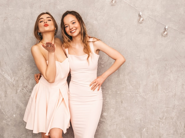 Two young beautiful smiling girls in trendy summer light pink dresses. sexy carefree women posing. positive models having fun. giving kiss Free Photo