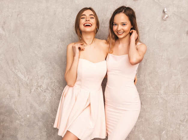 Two young beautiful smiling girls in trendy summer light pink dresses. sexy carefree women posing. positive models having fun Free Photo