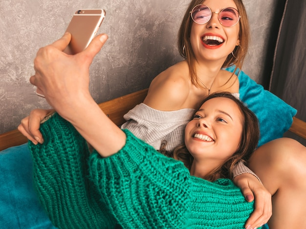Two young beautiful smiling gorgeous girls in trendy summer clothes.  sexy carefree women posing in interior and taking selfie. positive models having fun with smartphone Free Photo