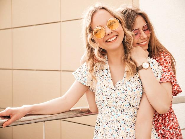 トレンディな夏のサンドレスで2人の若い美しい笑顔の流行に敏感な女の子。セクシーな屈託のない女性がサングラスで通りの背景にポーズします。楽しくてクレイジーになるポジティブモデル 無料写真