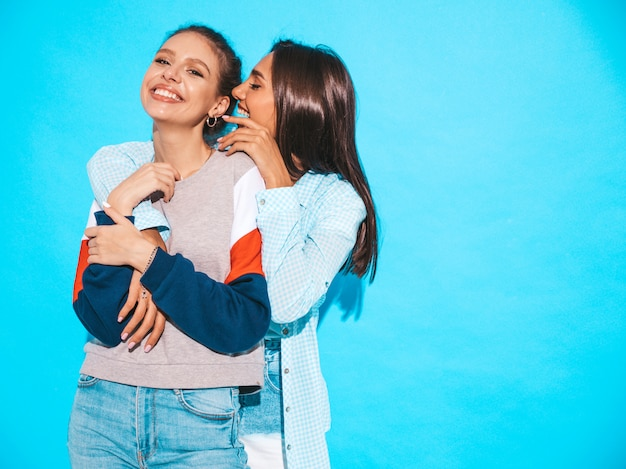 Two young beautiful smiling hipster girls in trendy summer casual clothes. sexy women share secrets, gossip.isolated on blue. surprised face emotions Free Photo