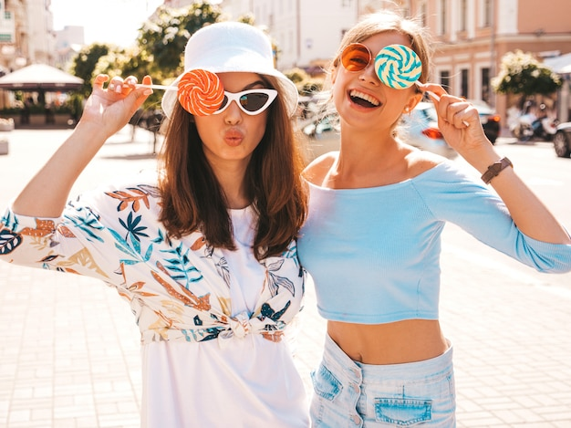 Two young beautiful smiling hipster girls in trendy summer clothes and panama hat. Free Photo