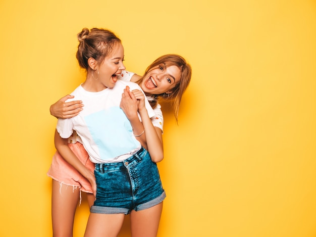 Two young beautiful smiling hipster girls in trendy summer clothes. sexy carefree women posing near yellow wall. positive models going crazy and having fun.hugging Free Photo