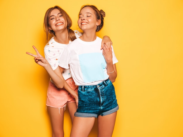 Two young beautiful smiling hipster girls in trendy summer clothes. sexy carefree women posing near yellow wall. positive models going crazy and having fun.shows peace sign Free Photo