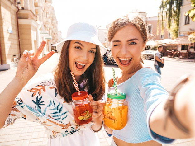 Two young beautiful smiling hipster girls in trendy summer clothes Free Photo