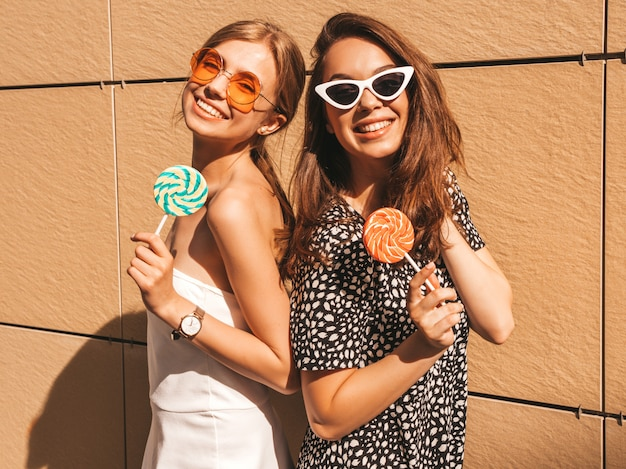 Two young beautiful smiling hipster girls in trendy summer dress. Free Photo