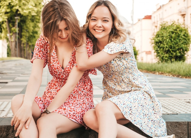 Two young beautiful smiling hipster girls in trendy summer sundress.sexy carefree women sitting on the street background. positive models having fun and hugging.they going crazy Free Photo