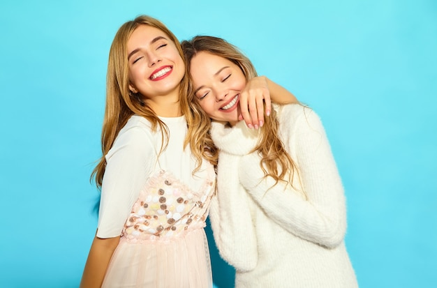 Two young beautiful smiling hipster women in trendy summer white clothes. sexy carefree women posing near blue wall. positive models hugging Free Photo