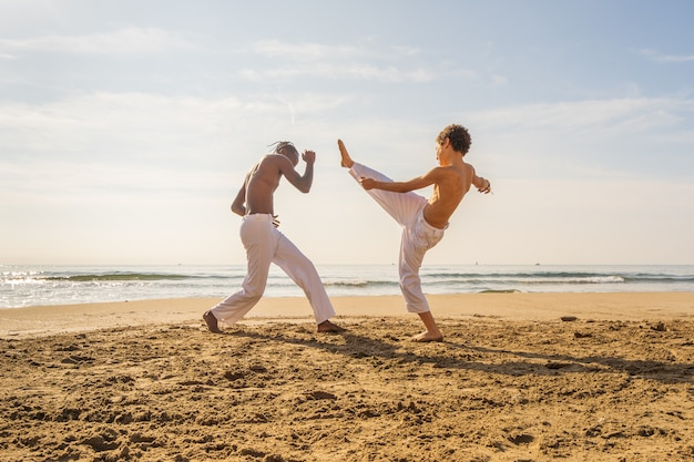 Two young brazilian in white pants practicing capoeira (brazilian martial art that combines elements of dance, acrobatics and music) on the beach Premium Photo
