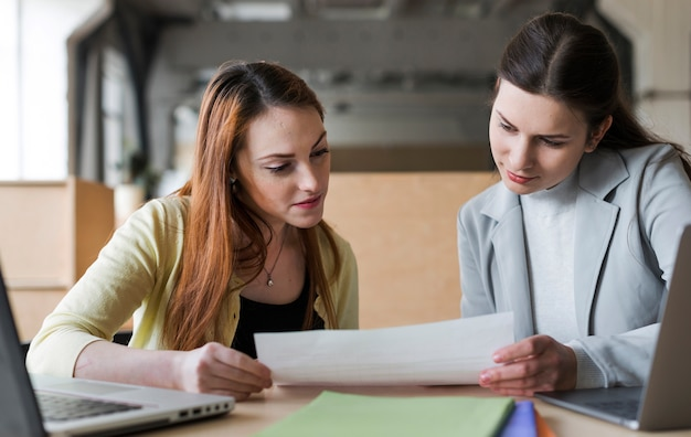 Two young businesswoman looking at paper in office Free Photo