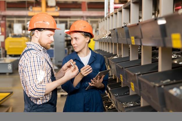 헬멧에 두 명의 젊은 자신감있는 컨트롤러와 건설 과정 전에 예비 부품의 균일 한 품질 검사 프리미엄 사진