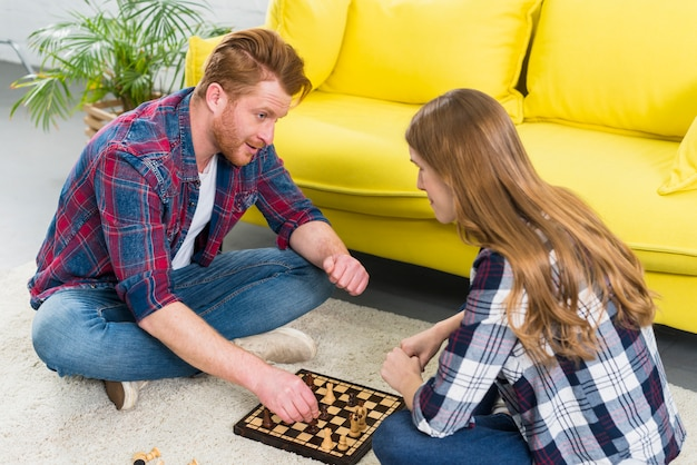 Two young couple playing the chess in the living room Free Photo