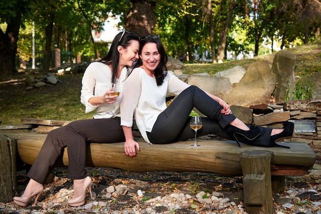 Two young cute girls sitting on logs drinking wine and laughing Premium Photo