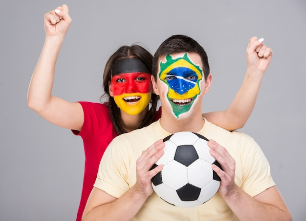 Two young fans with flags of their faces are holding a ball. Premium Photo