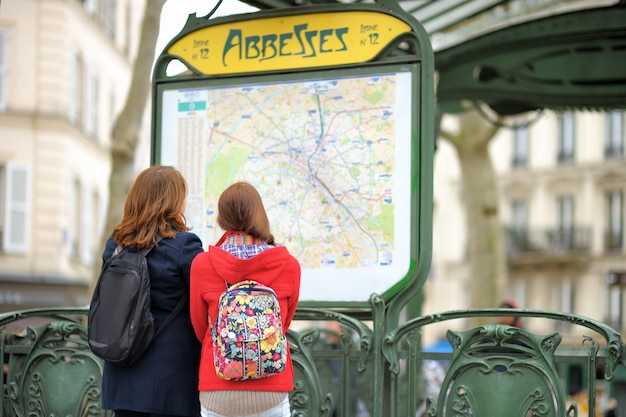 Two young female tourist looking at the map of parisian metro Premium Photo