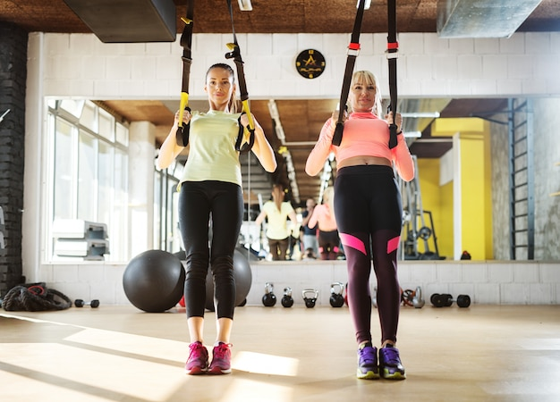 Premium Photo | Two young fit girls in a gym doing trx suspension training.