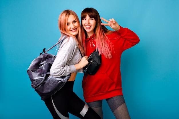 Две молодые забавные симпатичные хипстерские женщины в ярких спортивных костюмах позируют, улыбаясь, готовые к кроссфиту и фитнесу Бесплатные Фотографии