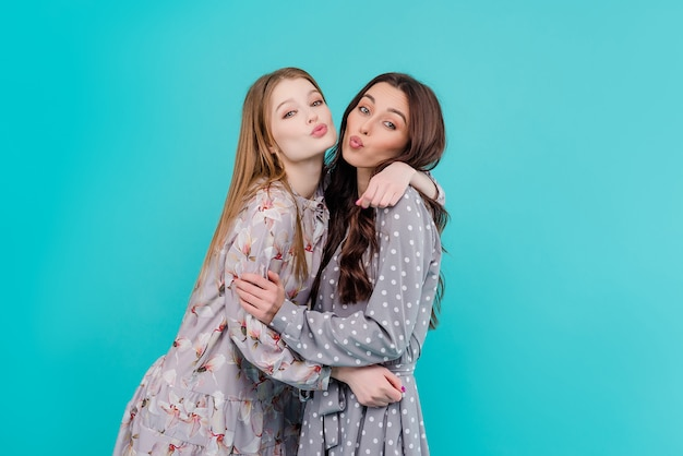 Two young girl friends hugging and kissing isolated Premium Photo
