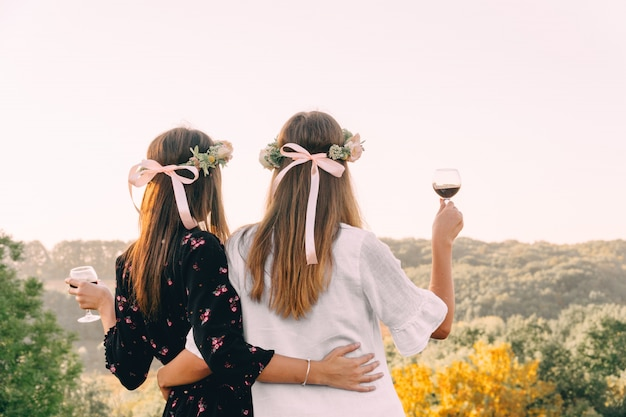 Two young girls hug during sunset in the field with wine glasses friendship concept Premium Photo