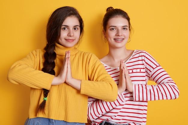 Две молодые девушки в повседневных рубашках позируют ладонями и улыбаются Бесплатные Фотографии