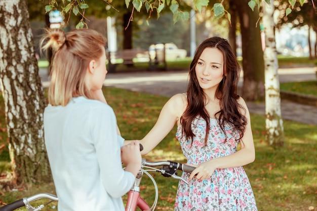 Две молодые девушки с велосипедами в парке Бесплатные Фотографии