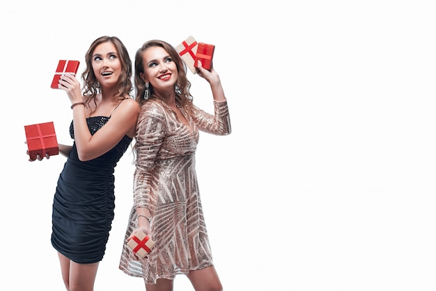 Two young girls with red presents in hands isolated on white Premium Photo