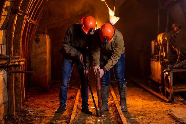 作業用の制服と保護用のヘルメットを着た2人の若い男が鉱山で作業 Premium写真
