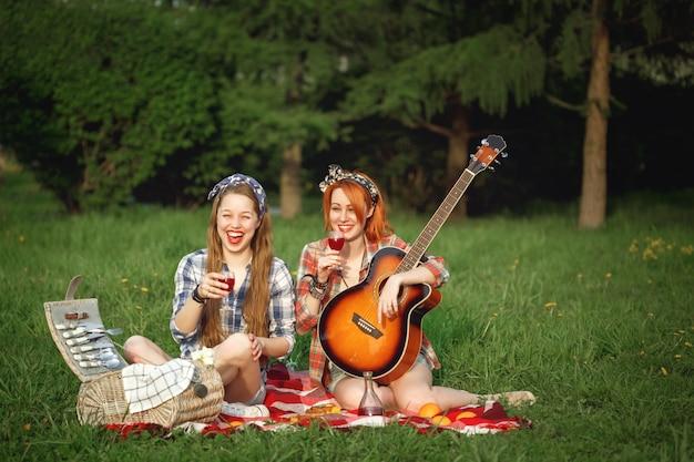 夏の公園でピクニックを楽しんでいる2人の若い流行に敏感な女の子 Premium写真
