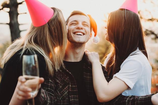 Две молодые дамы в праздничных шляпах улыбаются и целуют веселого парня с бокалом в щеках во время празднования рождества на природе Premium Фотографии