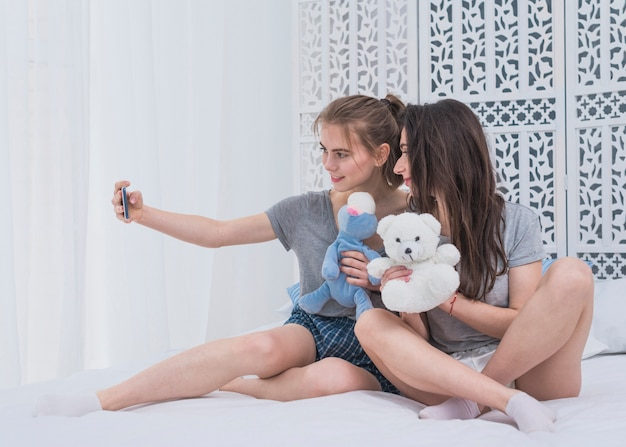 Two young lesbian couple sitting on bed taking selfie on mobile phone Free Photo