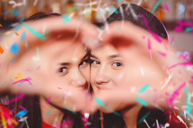 Two young lesbian girls make a heart with their hands Premium Photo