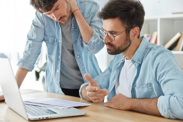 2人の若い男性起業家が一緒に財務報告書を作成し、ドキュメントを注意深く見ます 無料写真