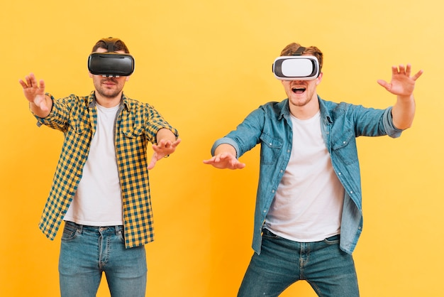 Two young man using virtual reality goggles touching in the air against yellow background Free Photo