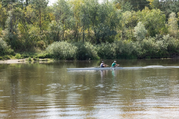 Двое молодых людей плывут по реке на байдарке. Premium Фотографии