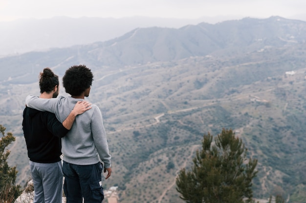 Two young men over looking the mountain landscape Free Photo