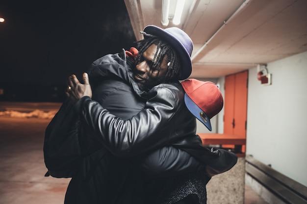 Двое молодых людей на улице автостоянка приветствия обнимаются Premium Фотографии
