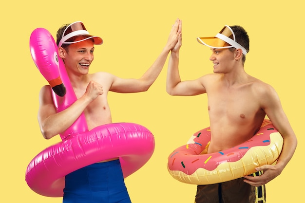 Ritratto di mezzo busto di due giovani uomini isolato. amici sorridenti in berretto con ciondoli. espressione facciale, estate, fine settimana, resort o concetto di vacanza. colori alla moda. Foto Gratuite