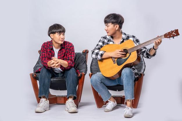 Due giovani uomini si sono seduti su una sedia e hanno suonato la chitarra. Foto Gratuite