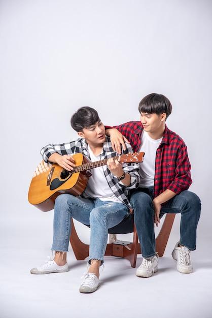 2人の若者が椅子に座ってギターを弾きました。 無料写真