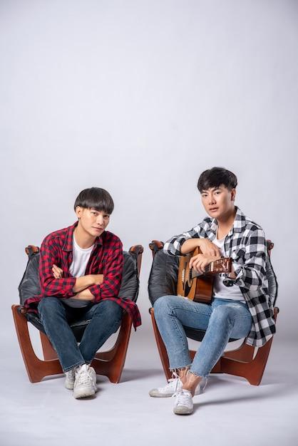 ギターを抱えて椅子に座っている2人の若い男性 無料写真
