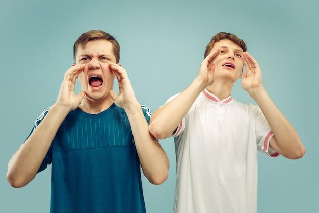 孤立したスポーツウェアに立っている2人の若い男性。スポーツ、サッカー、サッカーのクラブやチームのファン。友達の半身像。人間の感情、顔の表情の概念。 無料写真