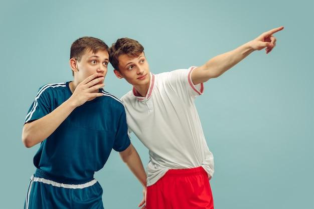 孤立したスポーツウェアに立っている2人の若い男性。ポインティングとショック。美しい男性モデルの半身像。人間の感情、顔の表情の概念。正面図。 無料写真