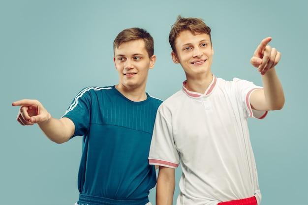Due giovani uomini in piedi in abbigliamento sportivo isolato. appassionati di sport, calcio o club o squadra di calcio. ritratto a mezzo busto degli amici. concetto di emozioni umane, espressione facciale. Foto Gratuite