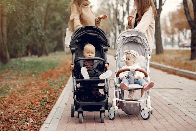 Two young mothers walking in a autumn park with carriages Free Photo