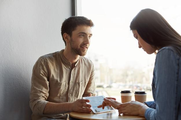 Два молодых предпринимателя встречаются, пьют кофе, рассказывают о будущем стартап-проекте и смотрят примеры дизайна веб-сайтов на планшете в кафетерии. производительное утро на удобной площади Бесплатные Фотографии