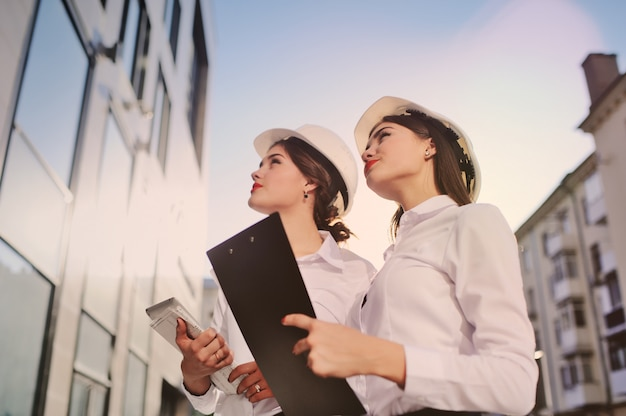 Two young pretty business women industrial engineers in construction helmets Premium Photo