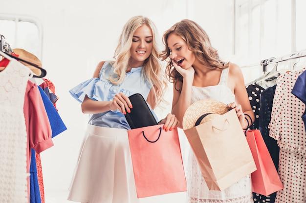 Le due ragazze carine guardano i vestiti e provano mentre scelgono in negozio Foto Gratuite