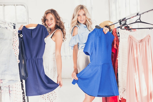 The two young pretty women looking at dresses and try on it while choosing at shop Free Photo